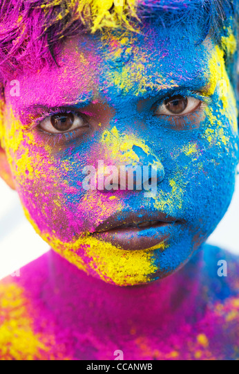 Young Indian boy covered in coloured powder pigment. India - Stock Image