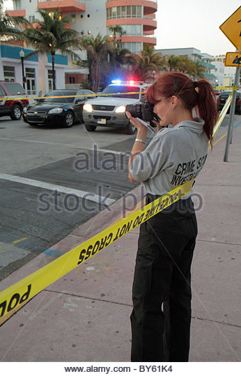Miami Beach Florida Ocean Drive accident bus bicycle rider collision police line do not cross tape woman camera - Stock Image