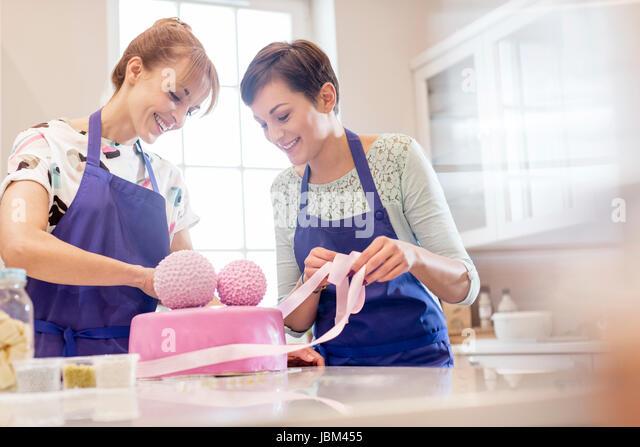 Female caterers finishing pink wedding cake in kitchen - Stock-Bilder