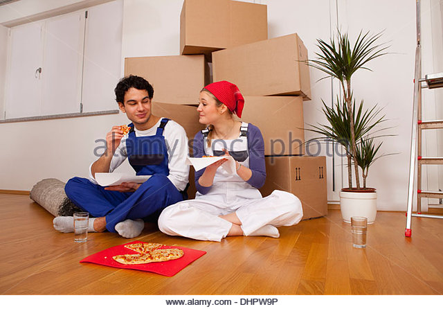 couple new home moving in eating pizza lunch break - Stock Image