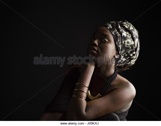 Portrait confident, serious African American woman wearing headscarf against black background - Stock Image