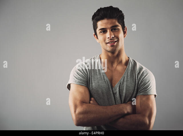 Portrait of handsome young man standing with his arms crossed against grey background with copy space. Hispanic - Stock Image