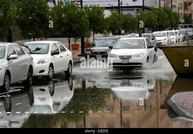 A taxi drives through the built-up rain water in the streets of Riyadh, Saudi Arabia - Stock Image