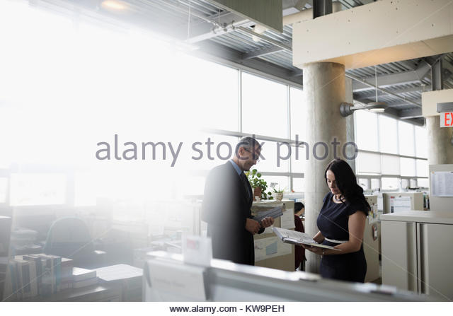 Businessman and businesswoman meeting,discussing paperwork in office - Stock Image