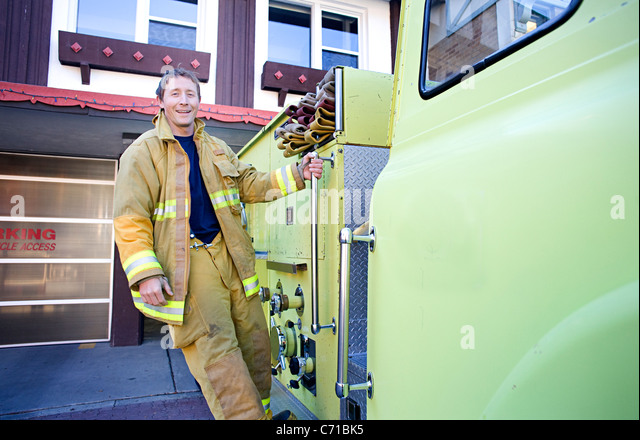 firefighter hangs on to side of fire truck - Stock Image