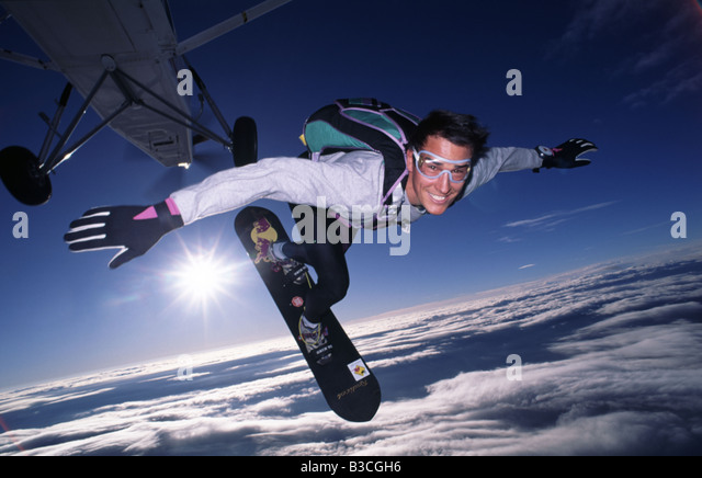 A Skydiver exits a Pilatus Porter PC6 with his surfboard The sun is in the background illuminating a thin cloud - Stock Image