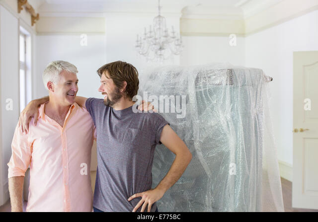Father and son hugging in living space - Stock Image