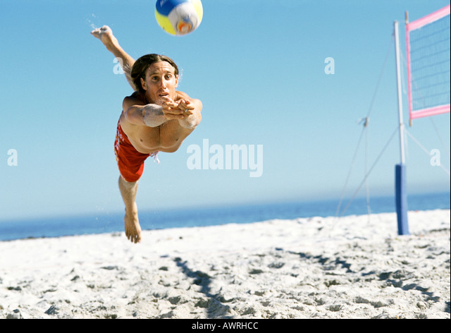 Young man jumping to hit volleyball, mid-air. - Stock Image