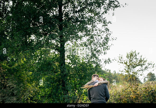 Image of a young couple hugging in a forest. Woman is holding a nice bouquet made of dry grass - Stock-Bilder