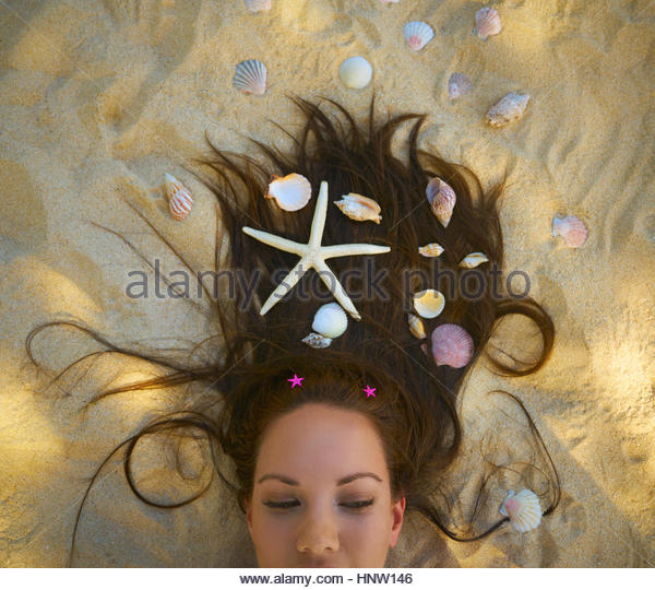 Pacific Islander woman laying on beach with seashells and starfish in hair - Stock-Bilder