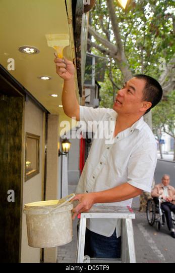Shanghai China Luwan District Xintiandi Fuxing Middle Road Asian man painter painting ladder small business paintbrush - Stock Image