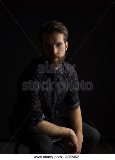 Portrait brunette man with beard in shadow against black background - Stock Image