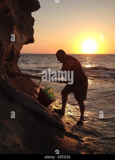 Fisherman preparing float and sail at dawn - Stock Image