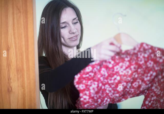 Young woman at home, deciding what to wear - Stock Image