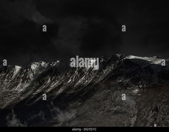 An ominous sky above a mountain range - Stock Image