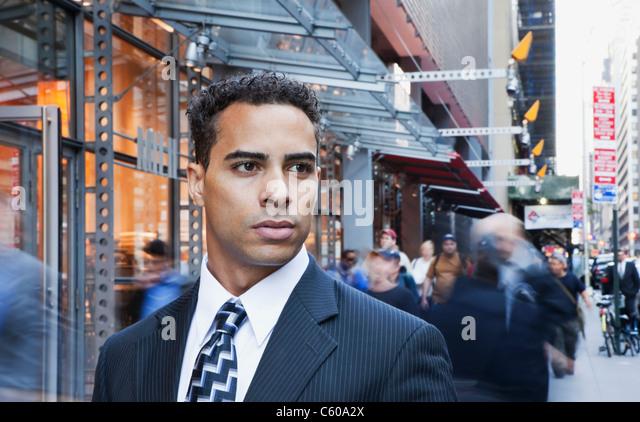 USA, New York, New York City, portrait of smiling businessman on street - Stock Image