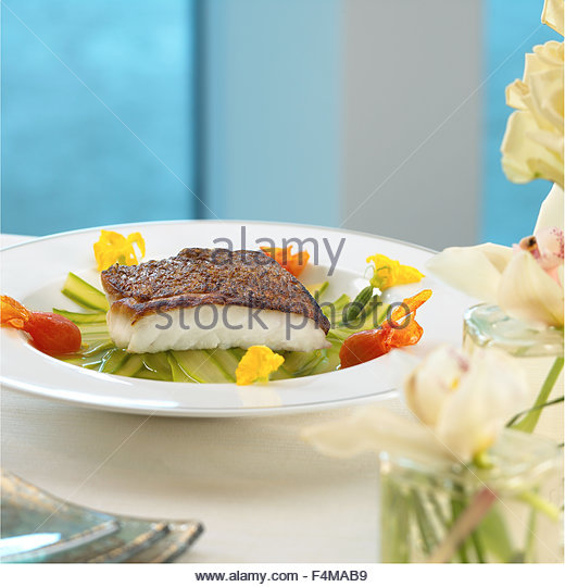 Pan roasted sea bass with zucchini ,and edible flowers - Stock Image