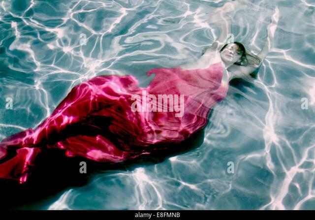 Woman in dress underwater - Stock Image