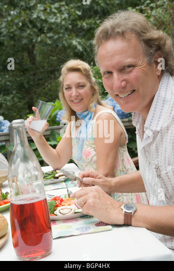 Portrait of a mature couple having breakfast and smiling - Stock-Bilder