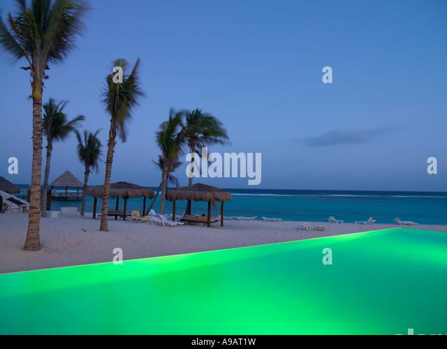 Mexico Quintana Roo Yucatan Peninsula Akumal Mayan Riviera infinity pool illuminated by the edge of a beach with - Stock-Bilder