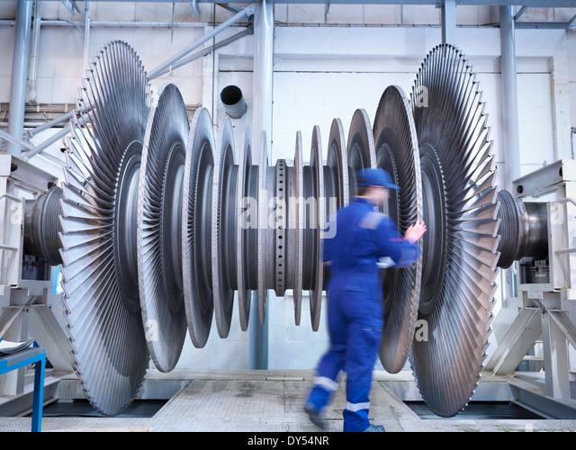 Engineer inspecting steam turbine blades in repair bay of workshop - Stock-Bilder