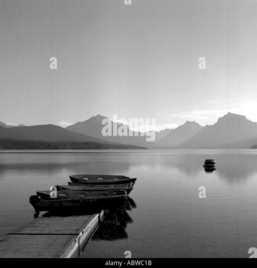 Black and white image of boats on a lake with mountains in the background. - Stock-Bilder