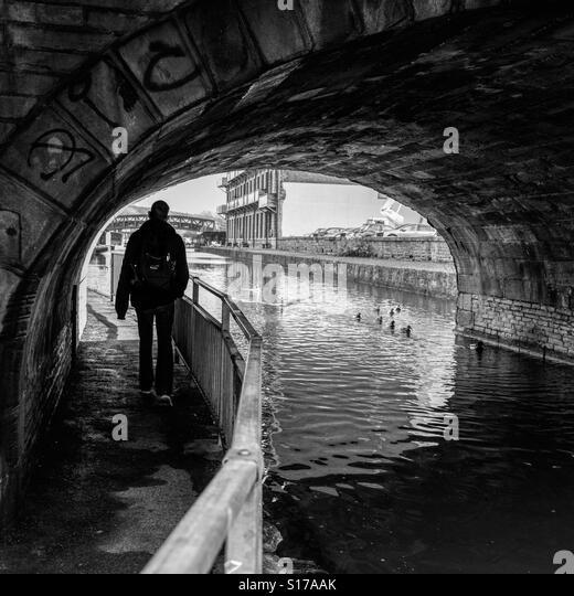 Man walking under a canal bridge in Brighouse, Calderdale , Yorkshire. - Stock-Bilder