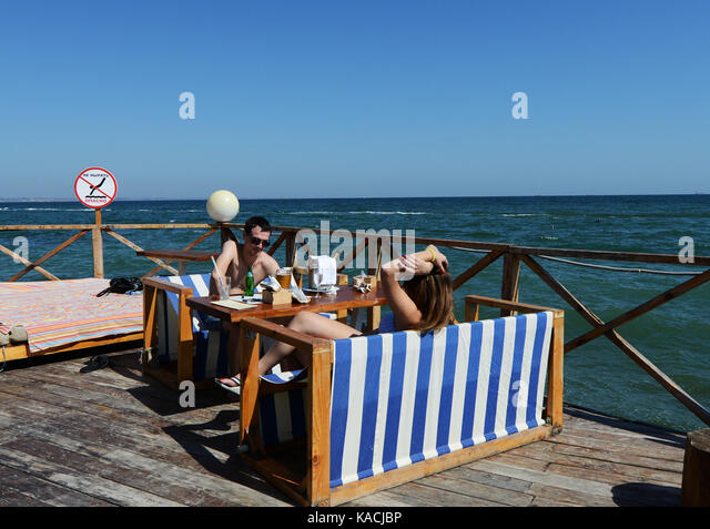 A couple relaxing by the sea at the  vibrant Otrada beach in Odessa, Ukraine. - Stock Image