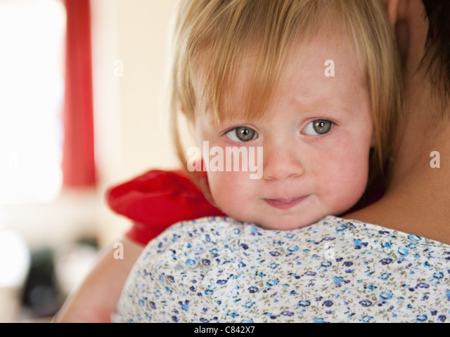 Toddler girl crying on mother's shoulder - Stock Image