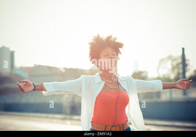 Young woman dancing with arms open to smartphone music in city - Stock Image