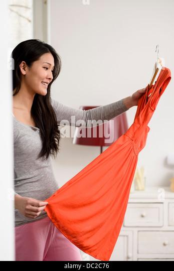 Smiling woman holding up orange dress - Stock Image