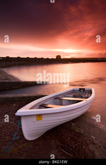 Fishing boat tethered on the shores of the Usk Reservoir at sunrise, Brecon Beacons National Park, Wales, UK. - Stock Image