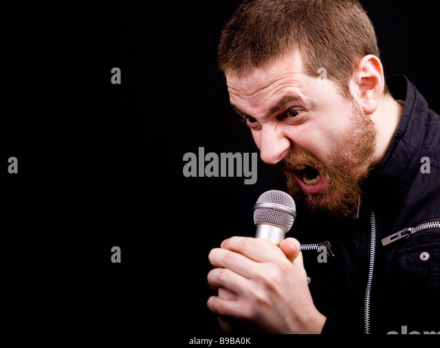 Scream of male angry rocker at the microphone with copyspace - Stock Image