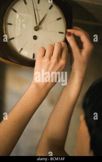 Woman adjusting clock, cropped view - Stock Image