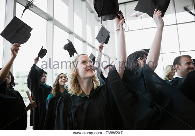 Enthusiastic college graduates throwing mortarboards overhead - Stock Image