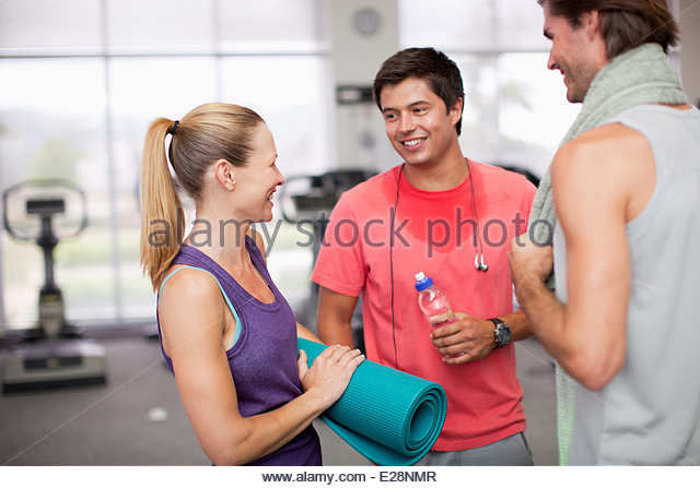 Woman with yoga mat talking to men in gymnasium - Stock Image