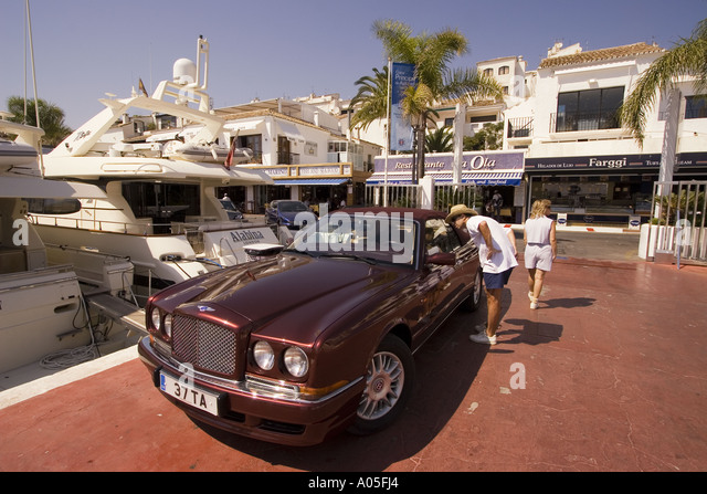Spain Puerto Banus Marbella Andalucia Bentley in front of luuxery yachts - Stock Image