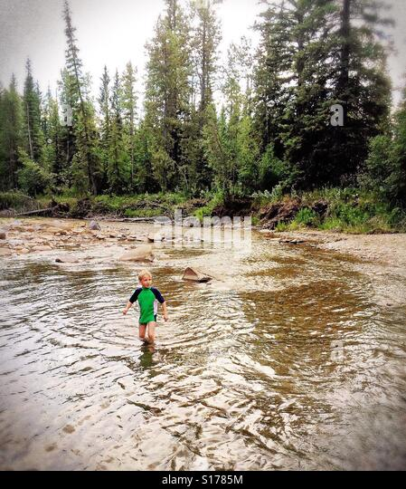 A young boy wades through a forest creek. - Stock Image
