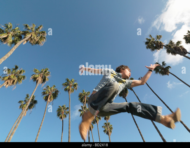 Man leaping in front of palm trees - Stock Image