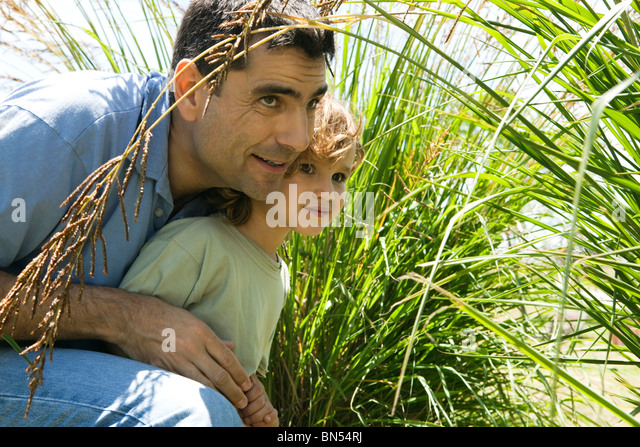 Father and son hiding in tall grass - Stock Image