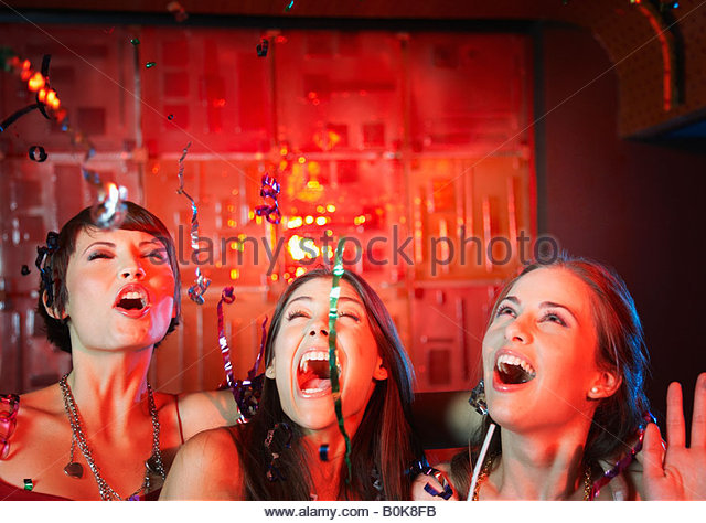 Three women in a nightclub drinking and laughing - Stock Image