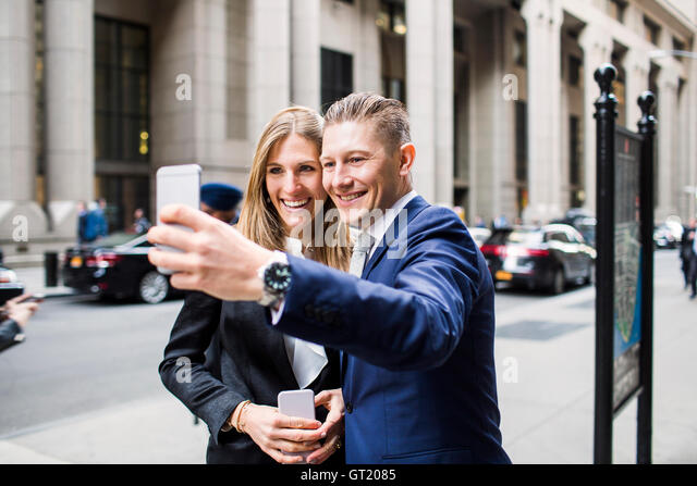 Smiling businessman and woman taking selfie while standing at city - Stock-Bilder