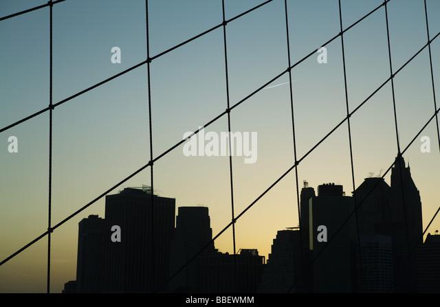 United States, New York City, silhouette of Manhattan skyline seen through Brooklyn Bridge - Stock-Bilder