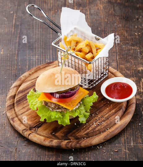 Burger and French fries in basket on wooden background - Stock Image
