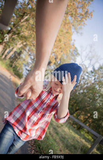 Sweden, Vastergotland, Lerum, View of father and daughter (8-9) walking on dirt road near Aspen lake - Stock Image