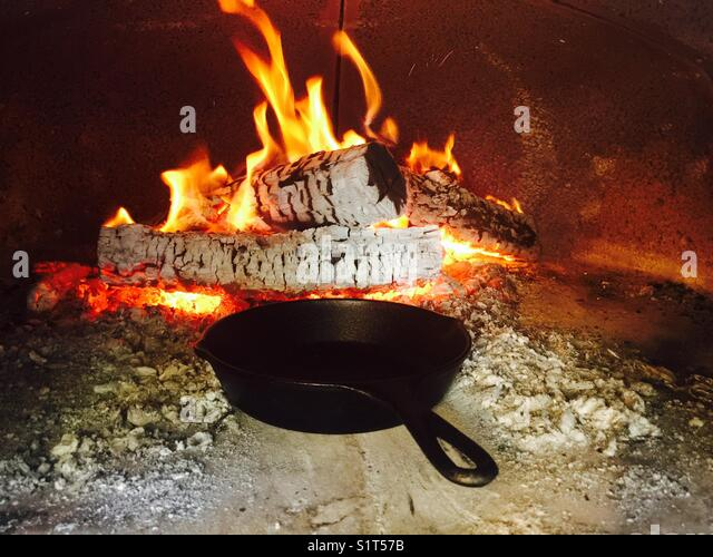 Wood fire oven warming cast iron pan - Stock Image