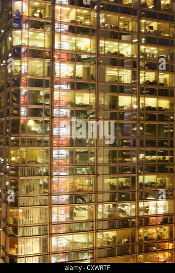 Urban office building lit up at night - Stock Image