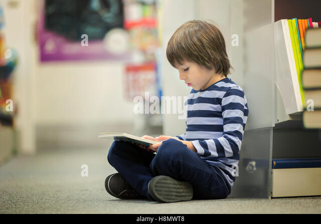Adorable little child, boy, sitting in a book store, reading books - Stock Image