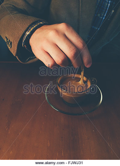 Cropped Hand Of Man Stirring Coffee At Table - Stock Image