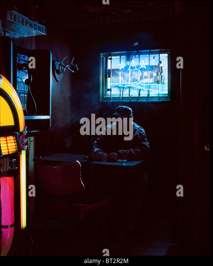 man drinking, interior of bar, lit daylight and neon, - Stock Image